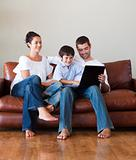 Parents and kid playing with a laptop on a couch