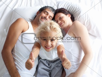 Happy little girl on bed with thumbs up and her parents