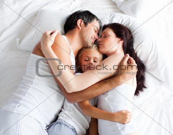 Little gril sleeping on bed with her parents