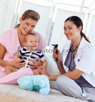 Baby with pediatrician and nurse smiling at the camera