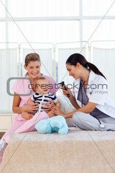 Baby playing with pediatrician and nurse