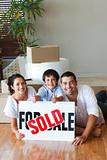 Family on the floor with boxes after buying house