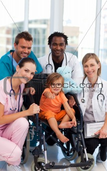 Baby girl in a wheelchair with medical team