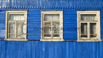 Three windows in the old blue wooden wall