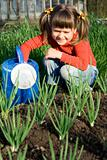 Smiling girl with watering can is sitting near onion patch