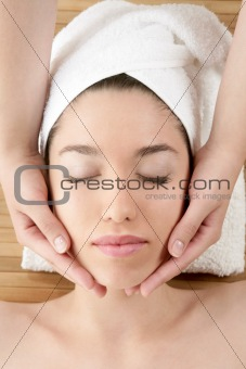 Beautiful woman face massage with white towel