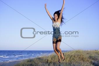 Beautiful brunette jumping in the beach