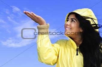 Beautiful young woman in raincoat checking for rain