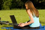 female student working with laptop outdoor