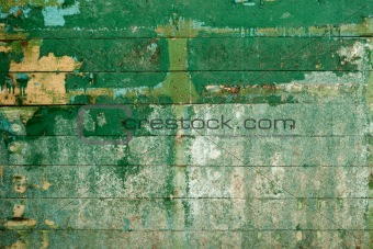 Green surface of the old wall covered with boards