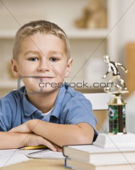 Boy Sitting in Front of Soccer Trophy