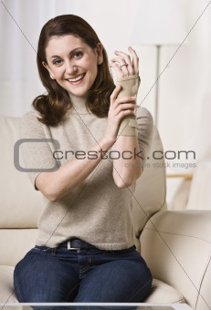 Woman Putting on Wrist Brace