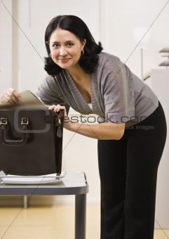 Attractive brunette looking in briefcase.