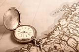 Old silver watch on old map