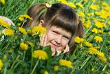 Little cute girl is lying on the dandelion meadow
