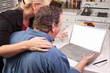 Couple In Kitchen Using Laptop with Blank Screen. Screen can be easily used for your own message or picture using the included clipping path.