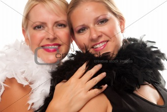 Portrait of Two Blonde Haired Smiling Girls with Feather Boas Isolated on a White Background.
