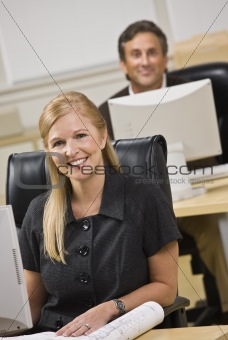 Attractive business people sitting at desks.