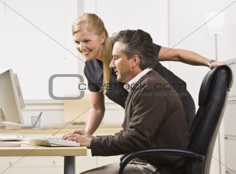 Attractive male and female working on computer.