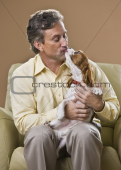 Attractive man kissing dog.