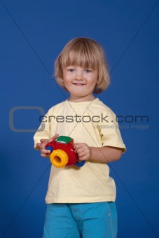 studio shot of a cheerful boy with a colorful plastic camera