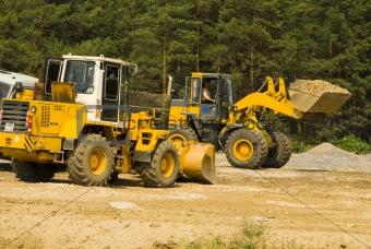 Heavy bulldozer loading ballast on the lorry