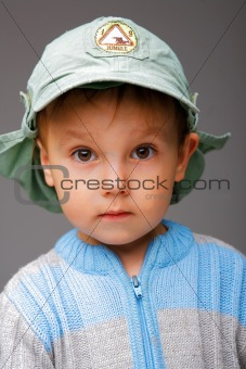 Closeup portrait of a little boy in a cap, serious attentive loo