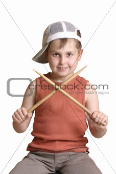 Boy with wooden drumsticks crossed.