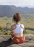 Lady sitting on the mountain top looking out into the view
