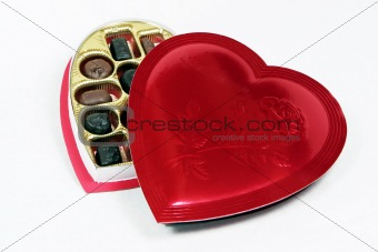 Heart shaped box of candy with lid partially on