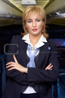 Blond air hostess (stewardess) in the empty ariliner cabin