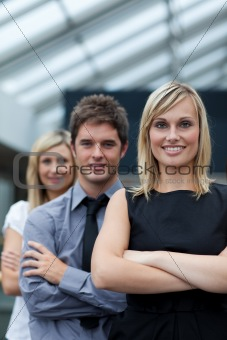 Beautiful businesswoman leading her team with folded arms