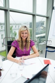 Smiling blonde businesswoman working in office