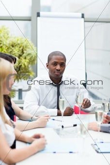 Afro-American businessman drinking champagne in office
