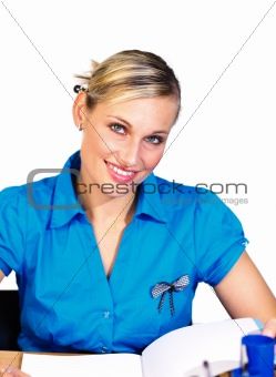 Blonde businesswoman reading and smiling at the camera