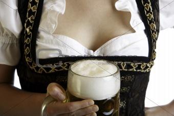 Bavarian beer girl holds Oktoberfest beer stein in front of brea