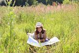 The girl on a summer meadow with a topographic map