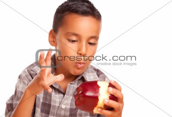 Adorable Hispanic Boy Eating a Large Red Apple Isolated on a White Background.