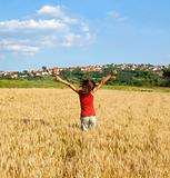 Happy girl jumping in wheat field