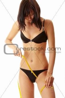 Slim woman measuring her leg
