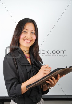 Attractive Asian girl writing in her notepad