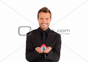 Smiling businessman holding house
