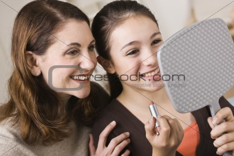 Smiling Mother and Daughter with Lipstick, Looking at Mirror