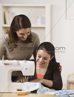 Mother Watching Daughter Use Sewing Machine