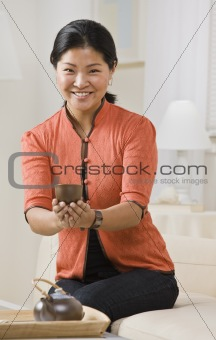 Asian woman serving tea.