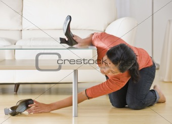 Asian woman reaching for shoe.