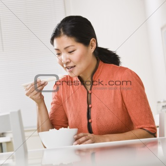 Asian woman eating rice.