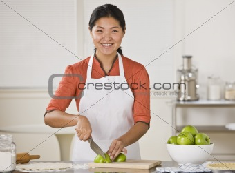 Asian woman slicing apples.