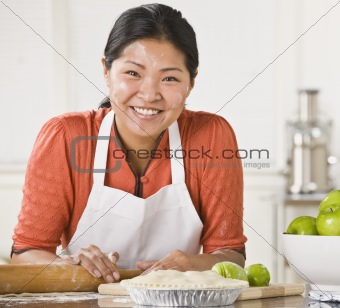 Asian woman making pie.
