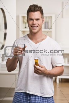 Attractive male with water and pills